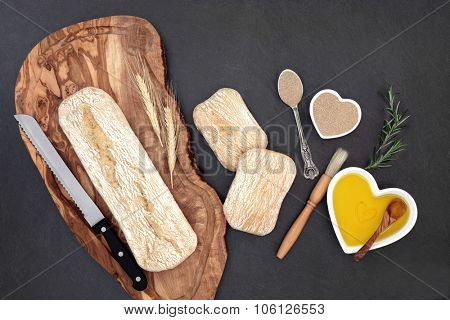 Ciabatta bread loaf on an olive wood board with wheat sheaths, rolls and baking ingredients of oil and yeast on slate background.