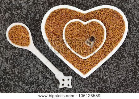 Bee pollen super food supplement in scoop and heart shaped dishes with bumblebee over marble background.