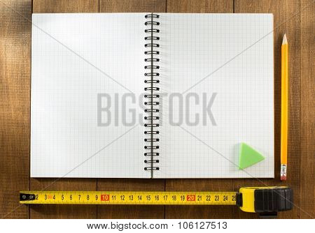 tape measure and pencil on wooden texture