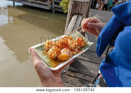 Holding mini Fried Mussels in Batter on the wood bridge