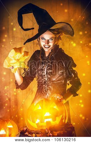 Enchanting witch and pumpkin with shining eyes. Halloween concept.