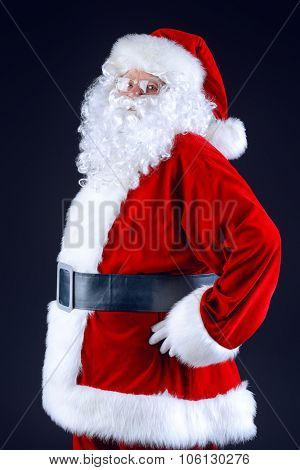 Portrait of Santa Claus standing sideways over black background. Christmas time.