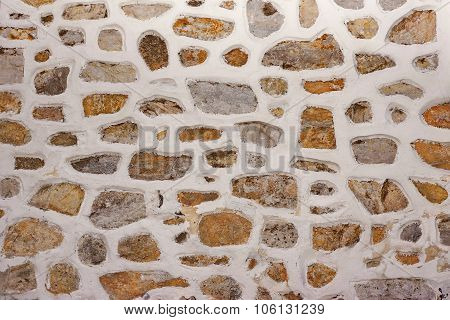 Stone Wall Made From Granite Rocks With White Honeycomb Pattern