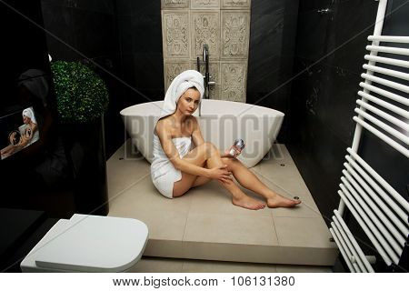 Beautiful woman applying cream on leg in bathroom.