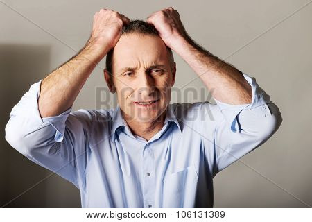 Portrait of frustrated man pulling his hair.