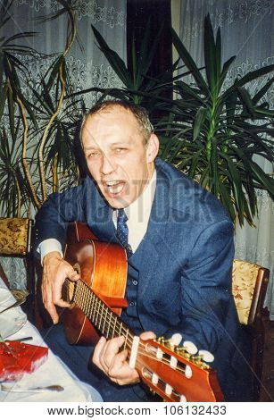 LODZ, POLAND, CIRCA 1990: Vintage photo of man playing guitar and singing during a family party