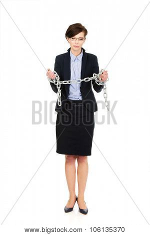 Guilty businesswoman wrapped with metal chain.