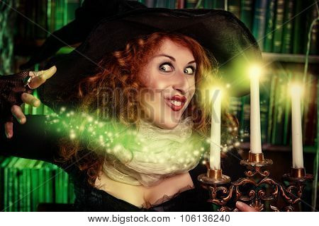 Portrait of a pretty funny witch in the wizarding lair. Fairytales. Halloween.