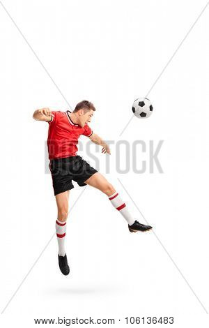 Full length portrait of a young football player heading a ball shot in mid-air isolated on white background