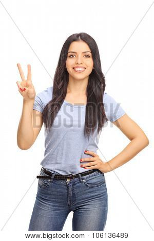 Vertical shot of a cheerful young woman making a peace sign with her hand and looking at the camera isolated on white background