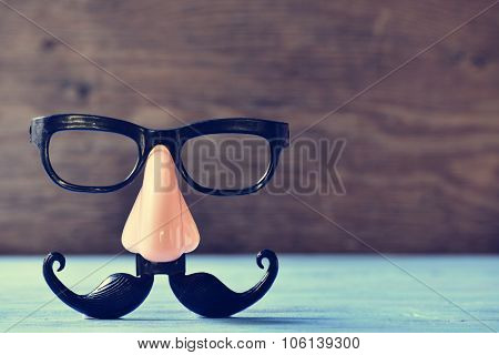 a fake mustache, nose and eyeglasses on a rustic blue wooden surface