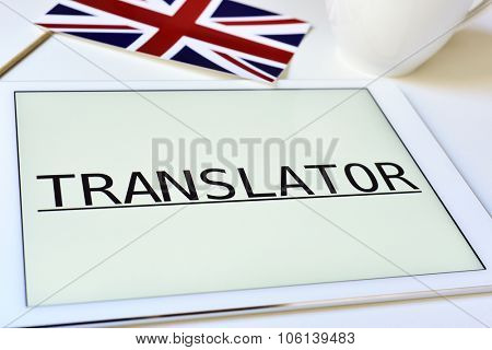 a flag of the United Kingdom and the word translator in the screen of a tablet computer, on a white table