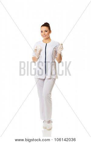 Smiling female nurse holding a drip.
