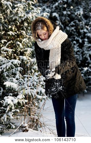 Teenage woman making snowball to fight
