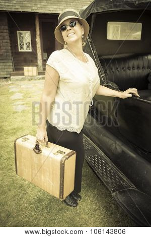Happy 1920s Dressed Girl Holding Suitcase Next to Vintage Car and Cabin.