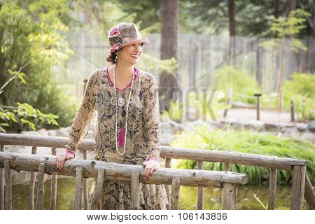 Attractive 1920s Dressed Girl On Wooden Bridge Portrait.