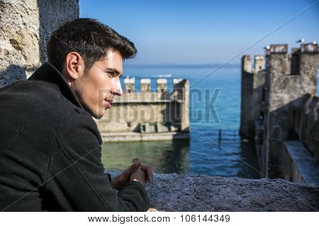 Young man in historic castle on Lake Garda in Sirmione, Italy