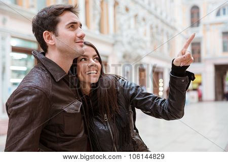Portrait of a happy woman pointing finger on something to her boyfriend outdoors in european city