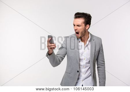 Portrait of a young businessman screaming on smartphone isolated on a white background