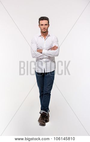 Full length portrait of a handsome man standing with arms folded isolated on a white background