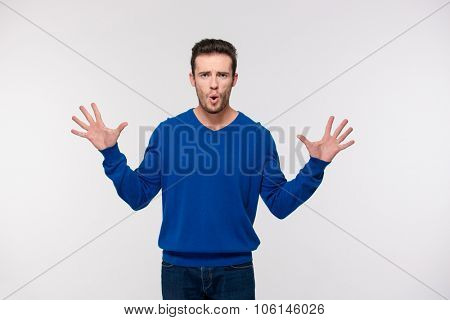 Portrait of a amazed man standing isolated on a white background