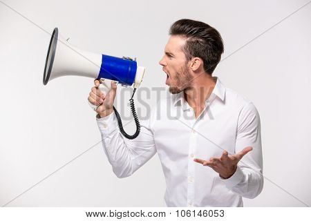 Portrait of a man yelling in megaphone isolated on a white background