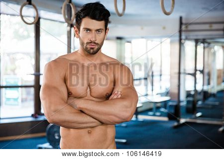 Portrait of a handsome man standing with arms folded in fitness gym and looking at camera