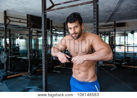 Portrait of a mucular male bodybuilder resting near parallel bars in fitness gym and looking at camera