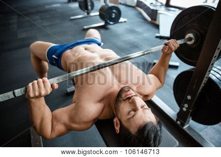 Portrait of a handsome muscular man doing bench press in fitness gym