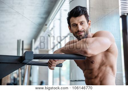 Portrait of a handsome man resting near parallel bars in fitness gym and looking at camera