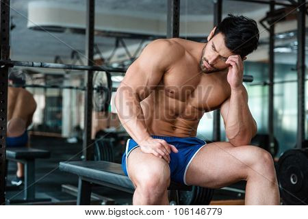 Portrait of a handsome muscular man resting on the bench in fitness gym