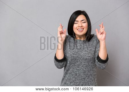 Beautiful asian girl in gray jumper keeping fingers crossed and eyes closed