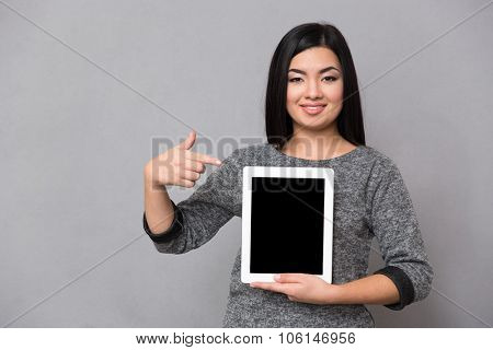 Beautiful happy smiling asian girl in gray jumper looking at camera staying and pointing on tablet computer