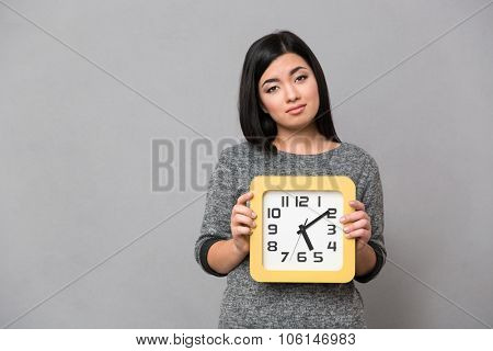 Portrait of a sad woman holding wall clock over gray background