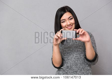 Beautiful happy smiling asian girl in gray jumper taking photos using cellphone