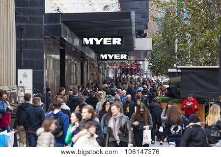 People walking along a busy street in Melbourne