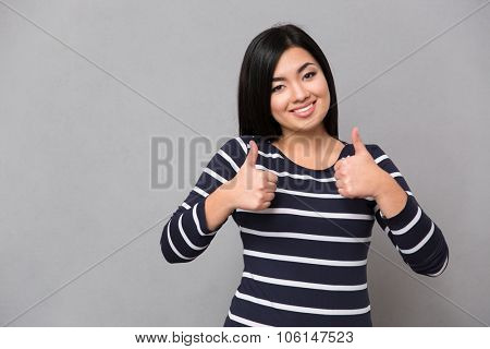 Beautiful happy smiling asian girl in striped jumper looking at camera giving thumbs-up