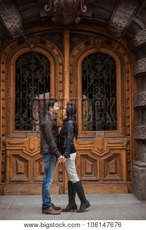 Full length portrait of a young couple flirting outdoors with old wooden door on background