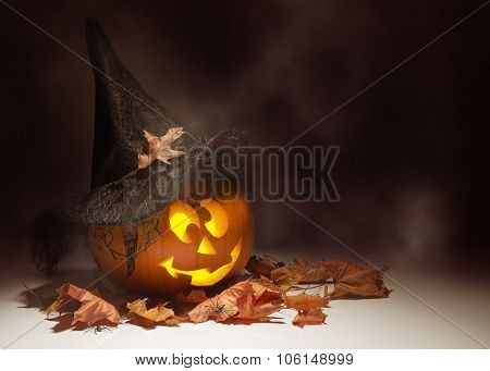 Glowing Jack O Lantern amongst autumn leaves