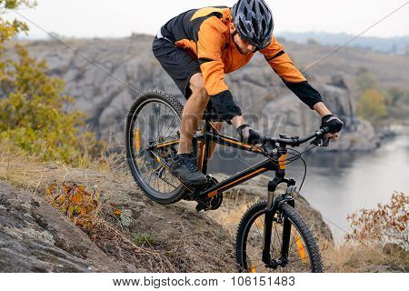 Cyclist in Orange Wear Riding the Bike Down Rocky Hill under River. Extreme Sports Concept.