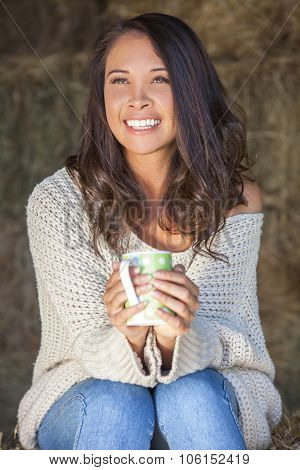 Beautiful happy Asian Eurasian young woman or girl smiling sitting in sunshine on a hay bale in a barn drinking tea or coffee