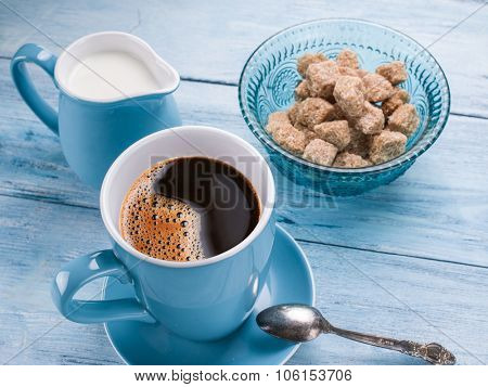 Cup of coffee, milk jug and cane sugar cubes on old blue wooden table.