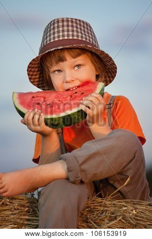 boy eating watermelon on a haystack