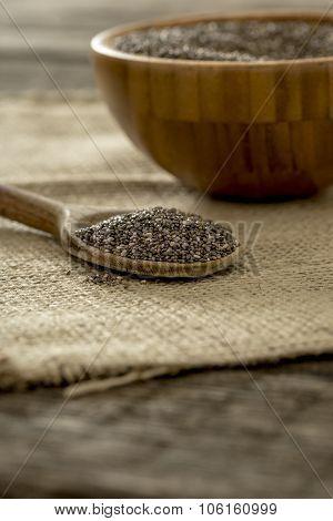 Wooden Spoon Full Of Chia Seeds Lying On Burlap Sac