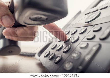 Closeup Of Male Hand Holding Telephone Receiver While Dialing A Telephone Number