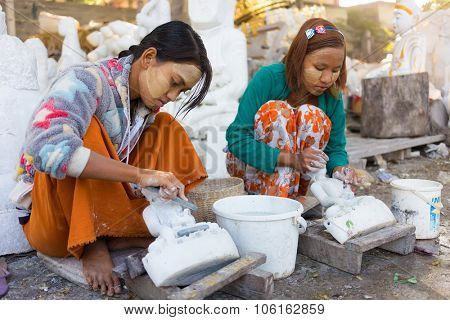MANDALAY, MYANMAR, JANUARY 20, 2015 : Young women are carving traditional marble Buddha statues, sitting in a street of Mandalay, Myanmar (Burma).