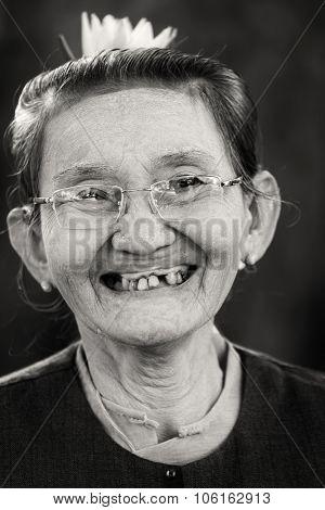 BAGAN, MYANMAR, JANUARY 24, 2015 : Black and white portrait of a sweet and cheerful senior Burmese woman in the village of old Bagan, Myanmar (Burma).