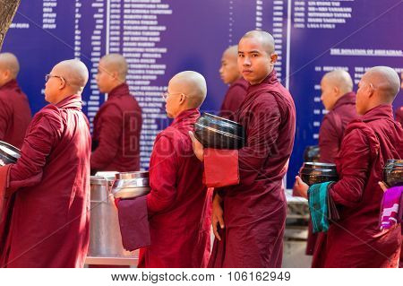 AMARAPURA, MYANMAR, JANUARY 20, 2015 : Monks are queuing holding their bowls to collect the unique daily meal at noon in the Mahagandayon monastery near Mandalay, Myanmar (Burma).