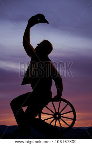 Silhouette Cowboy Sitting On Wagon Wheel Hold Hat Up