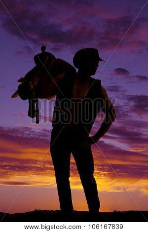 Silhouette Of A Cowboy Holding A Saddle On Shoulder Hand On Hip